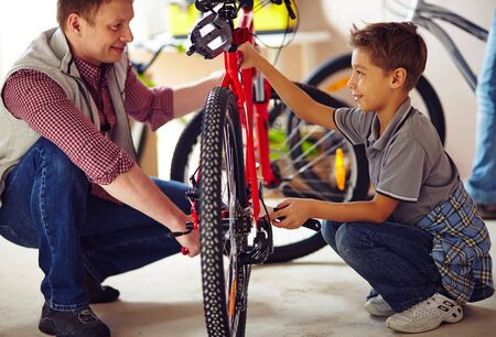 Father with his son repairing a bike together photo
