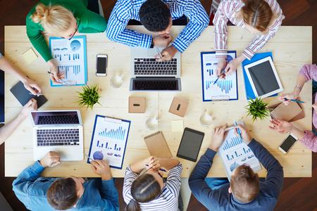 Sopra vista business team seduti intorno a tavola e di lavoro