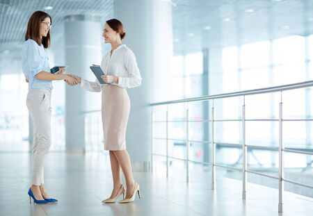 Office women: Female colleagues meeting in corridor of office building