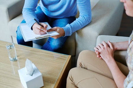 Male psychologist making notes during psychological therapy Stockfoto
