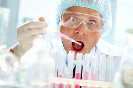Surprised man in mask looking at test tubes photo