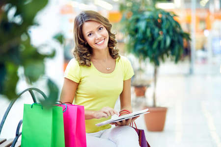 touchpad: Young pretty woman using touchpad while sitting in the mall