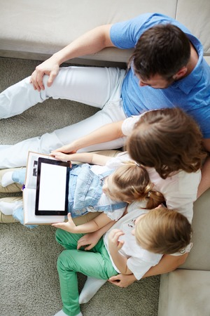 mom son: High view of family using touchpad together at home