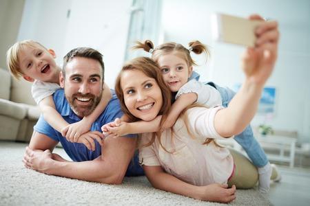 家庭: 快樂年輕的家庭在家裡採取自拍照在地板上