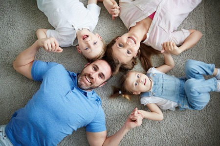 Portrait of happy family lying on floor Stock Photo