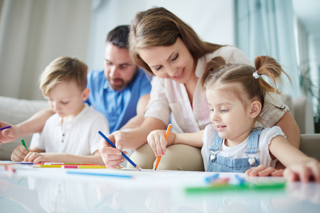 family together: Mother helping her little daughter to draw