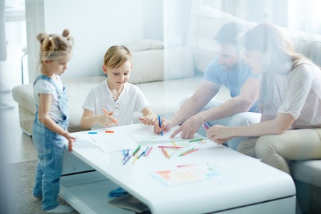 family together: Children drawing at the table with their parents