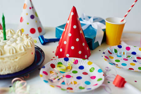 cake plate: Empty plates with cake and hats on decorated table