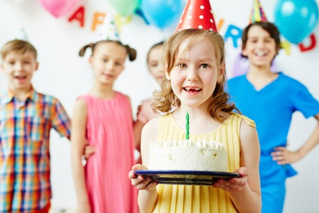 party pastries: Little girl holding birthday cake and smiling Stock Photo