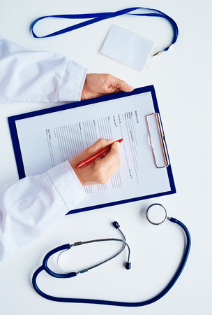 clinician: Hands of clinician with pen over medical card in clipboard