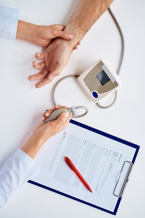 therapeutist: Hands of therapeutist with tonometer measuring blood pressure of patient
