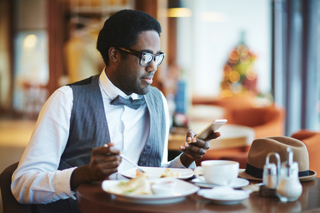 african people: Elegant young man with cellphone eating in cafe
