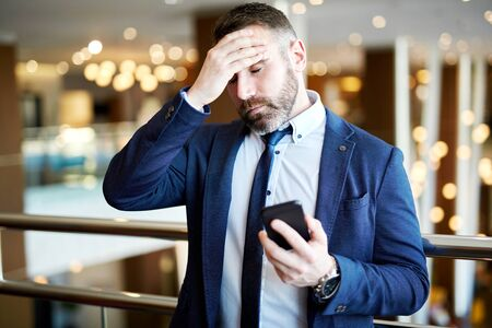 tense: Fatigue man with cellphone touching his forehead
