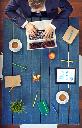 High angle view of businessman using laptop at desk in office photo