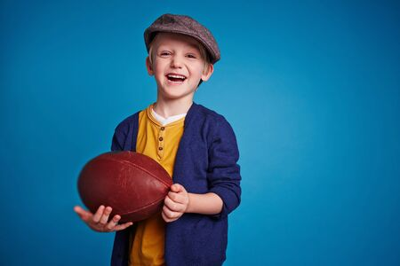 child laughing: Little boy standing with rugby ball and laughing