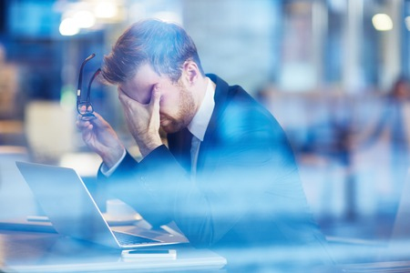 people on computers: Depressed businessman sitting with laptop