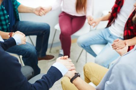 Groep mensen zitten in een cirkel en elkaar te steunen Stockfoto