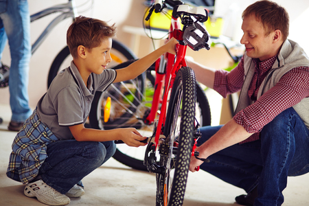 Father helping his son fix a bicycle photo