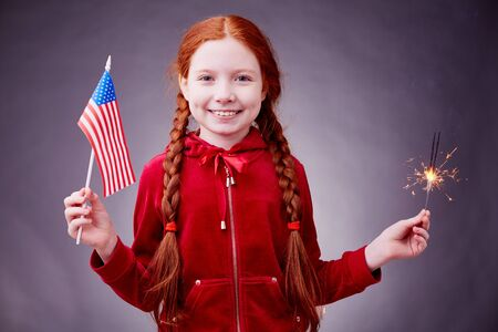 Portrait of a cheerful girl with American flag and Bengal light
