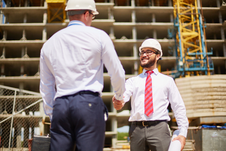 hard hats: Young businessmen in hard hats shaking hands