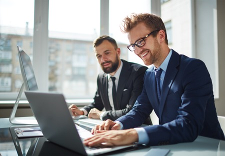 business partners: Two business partners working with laptop together Stock Photo