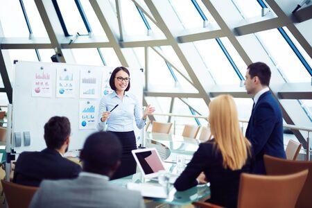 Jeune employé donnant une présentation à des gens d'affaires