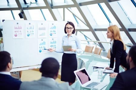 Giovane donna di affari che presenta statistiche finanziarie ai suoi partner alla conferenza
