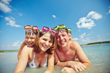 mom son: Happy parents with their sons swimming together Stock Photo