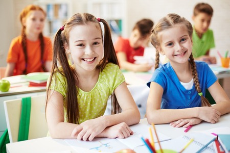 elementary schools: Portrait of two schoolchildren sitting at the desk and smiling at camera Stock Photo