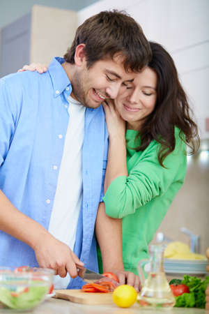 home cooking: Young woman embracing her husband while he cutting fresh tomato