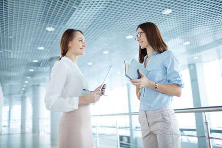 women smiling: Portrait of two confident businesswomen planning work Stock Photo