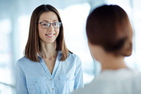 colleagues: Young businesswoman listening to her colleague Stock Photo