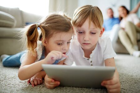 modern parents: Modern kids with touchpad networking with parents on background