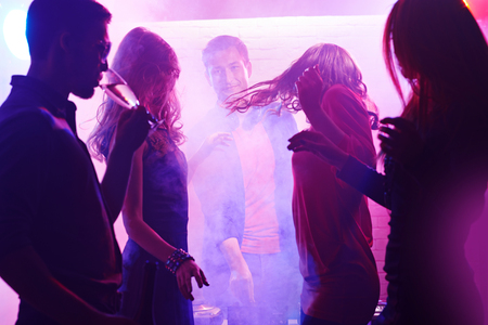 clubber: Energetic girls dancing at disco Stock Photo
