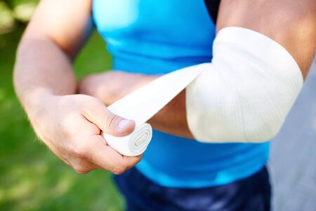 contusion: Young man bandaging his arm Stock Photo