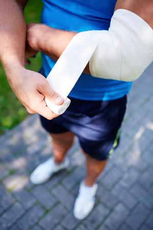 codo: Joven deportista vendaje de la articulación del codo fuera