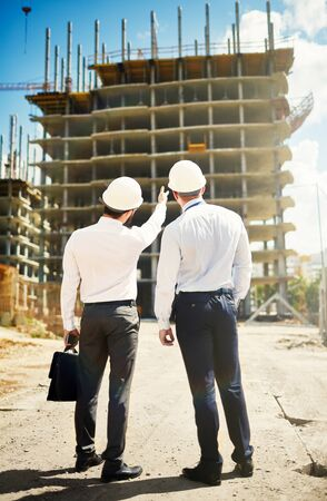 coworker: Young architect showing new construction to co-worker Stock Photo