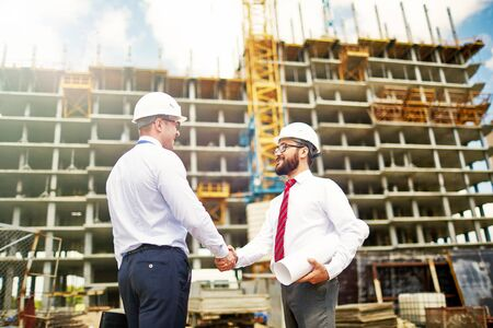 trust people: Handsome architects in helmets handshaking by new construction Stock Photo