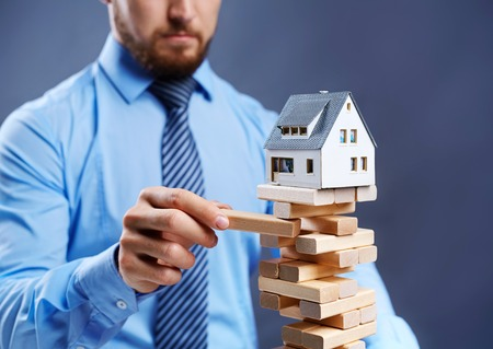 tower house: Modern businessman taking out wooden block from tower with toy house on its top