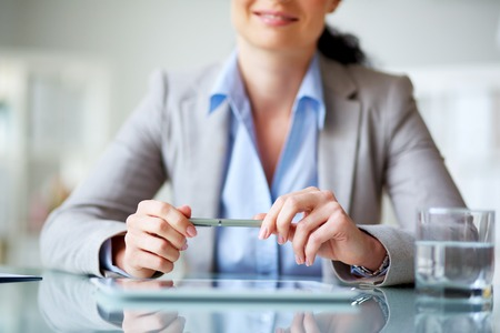 modern businesswoman: Modern businesswoman holding pen in hands Stock Photo