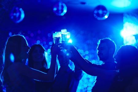 Gruppe glückliche Freunde an der Party im Nachtclub rösten
