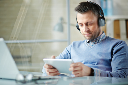 obsessed: Obsessed businessman with headphones listening to music and using touchpad