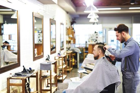 cutting hair: Modern barber cutting hair of his client Stock Photo