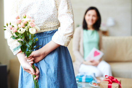 gift behind back: Girl holding flowers for her mother Stock Photo