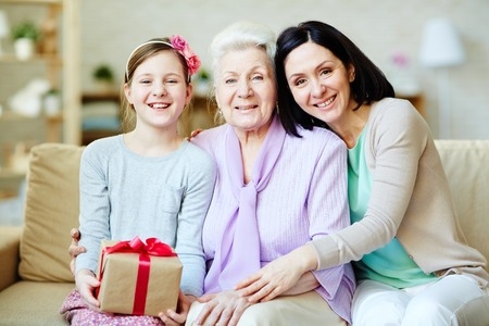 Young woman, elderly one and cute girl with gift-box looking at camera