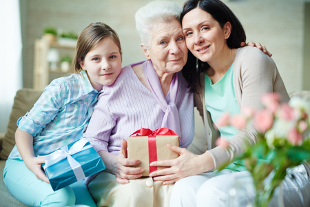 Young woman, elderly one and teenage girl with presents looking at camera