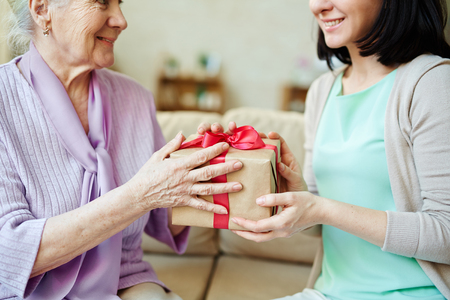 Young woman giving package with surprise to her mother Imagens