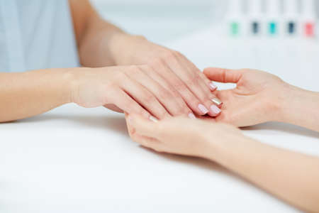 nailcare: Female hands with polished fingernails held by manicurist