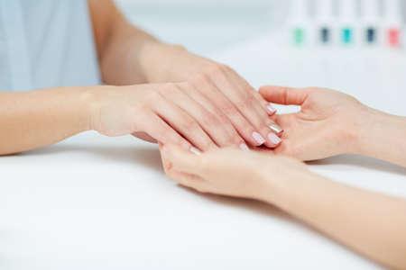 manicurist: Female hands with polished fingernails held by manicurist