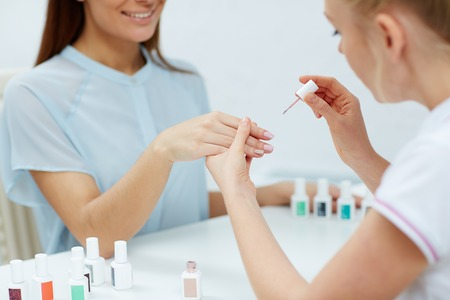 nailcare: Manicurist polishing fingernails of her client in beauty salon Stock Photo